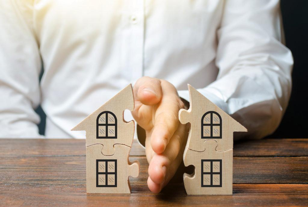 Maison en pièce de puzzle en bois avec une main d'homme la séparant en deux